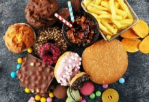 Junk food, including ice cream, hamburgers and fries, arranged on a table