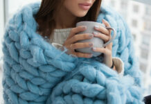woman snuggling up with cup of tea